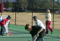 Students practicing hockey on tennis court