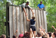 College students scaling wall on ropes course