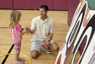 Pre-school student receiving tennis ball to throw